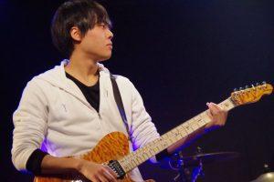 ライブでギターを弾いている三輪さんの横顔の画像。