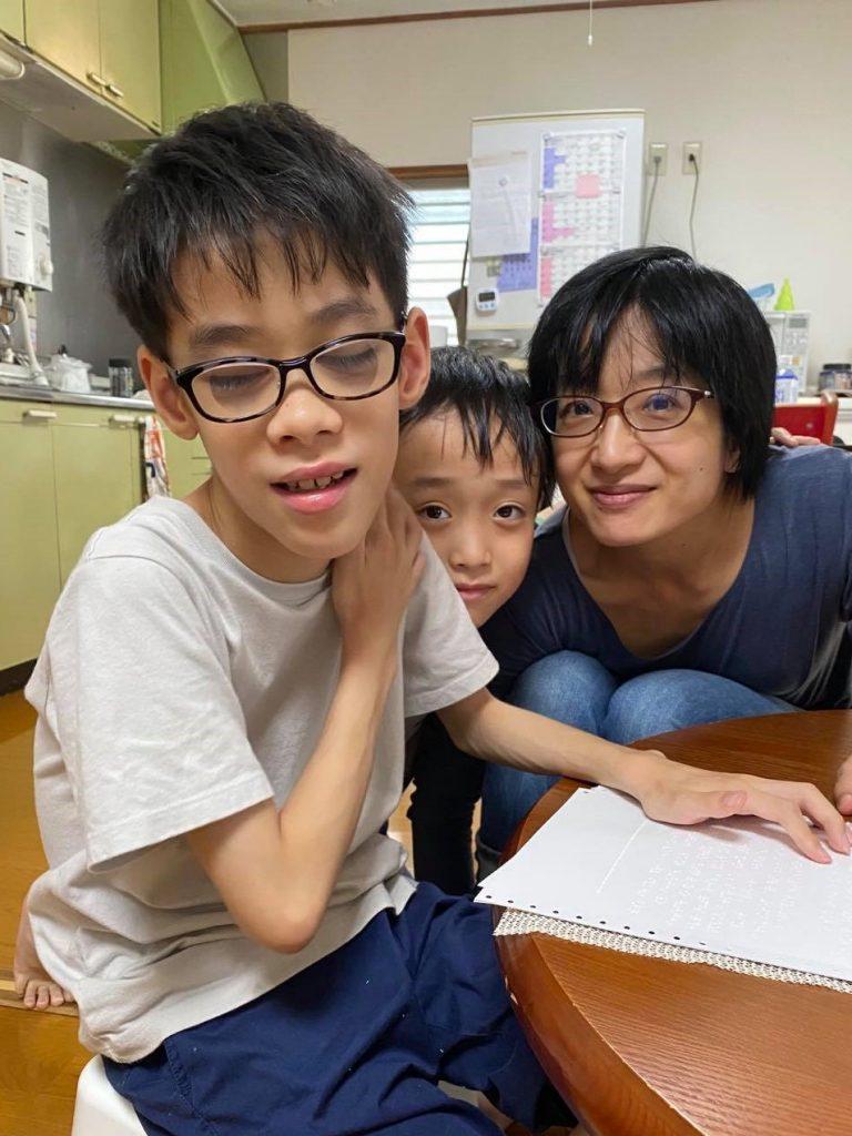 自宅で長男が点字で勉強している途中、次男と佳子さんの3人がカメラ目線で映っている画像。