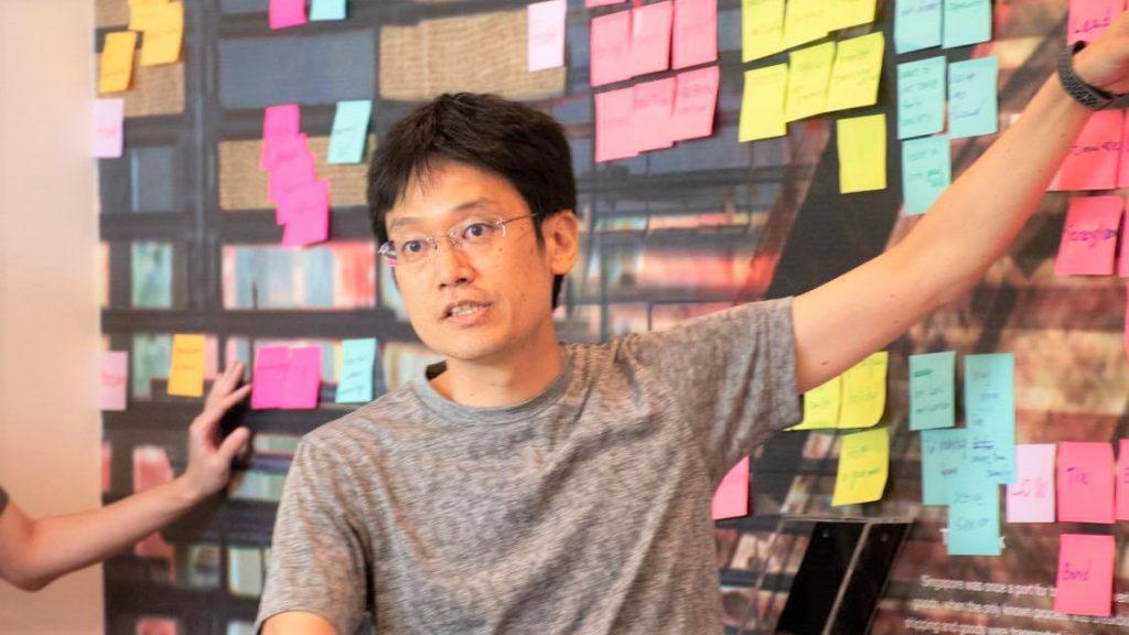 百田さんがボードにたくさん貼ったポストイットを指さしながら話をしている画像。