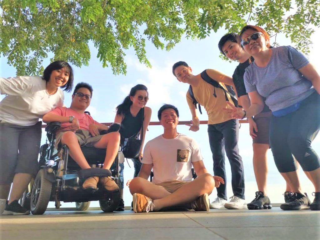 海を背景に、百田さんが海外の障害者と一緒に記念撮影している画像。