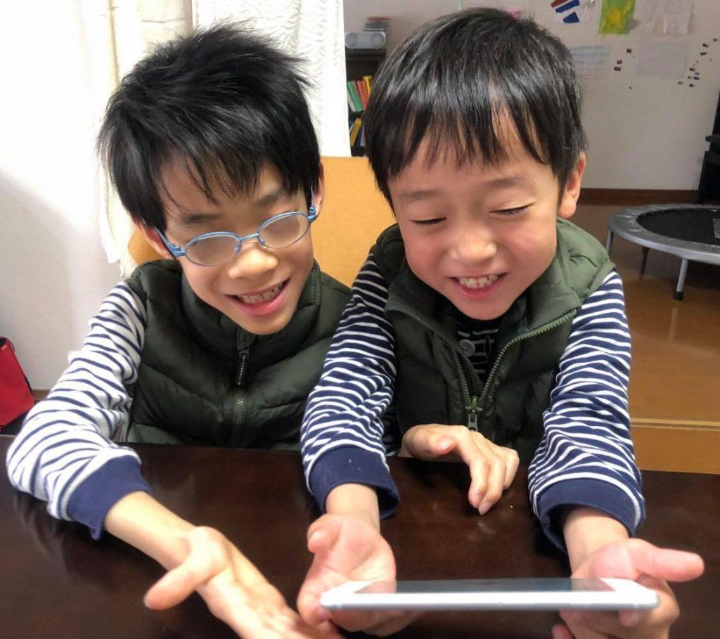 1台のアイパッドを兄弟2人が笑顔で操作している画像。