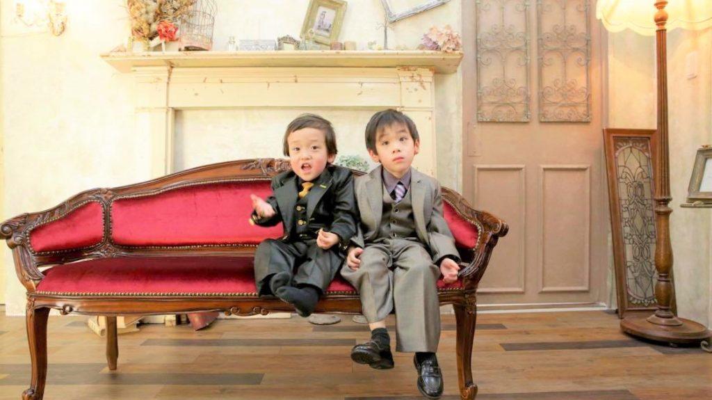 兄弟2人が写真館で正装して、驚いた表情で写っている画像。