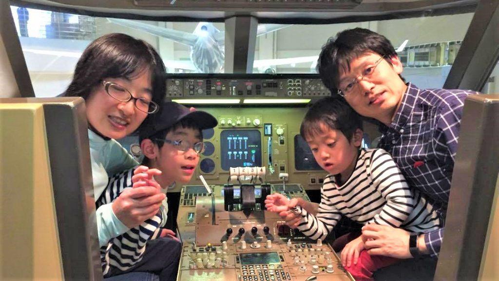 飛行機の運転席に家族4人で座って記念撮影している画像。