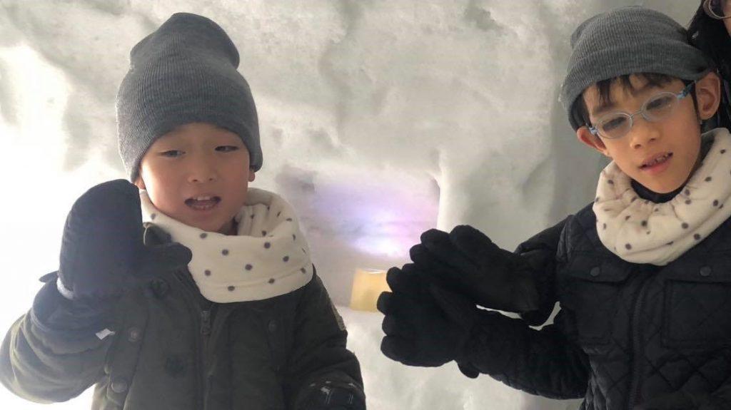 雪の中、兄弟が笑顔で記念撮影している画像。