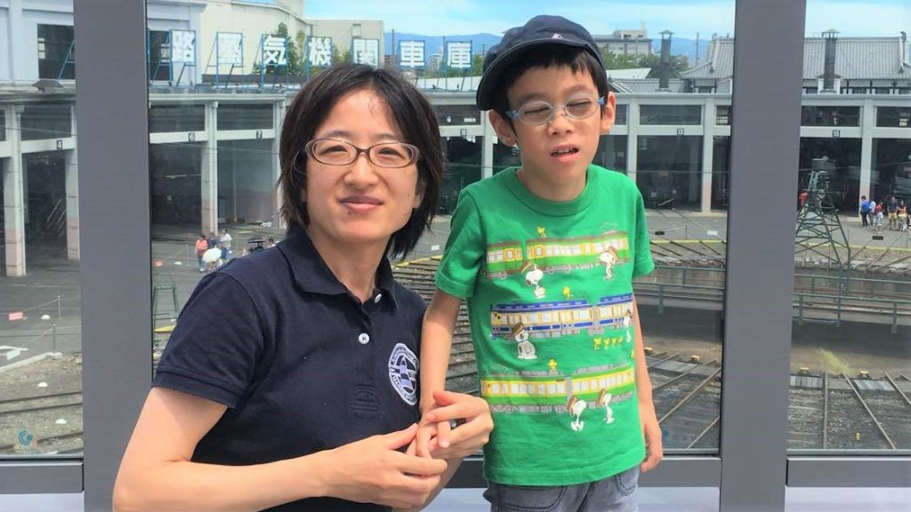 蒸気機関車の工場見学で佳子さんとご長男が記念撮影している画像。