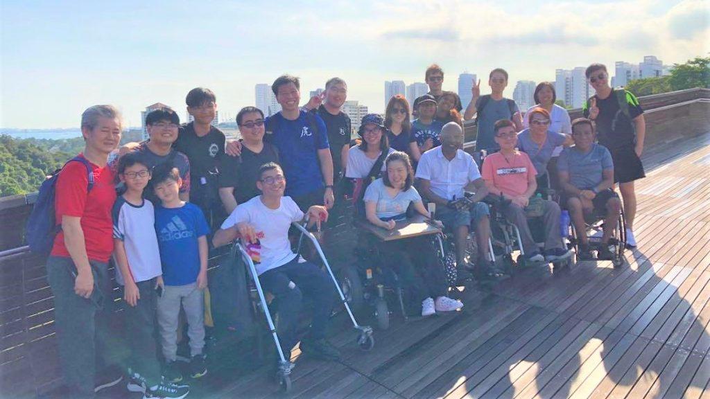 障害者や健常者が一緒になり、景色のいい場所で記念撮影している画像。