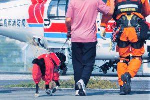 盲導犬を連れた清水さんが消防隊と一緒にヘリコプターに向かっていく様子を後ろから撮影した画像。