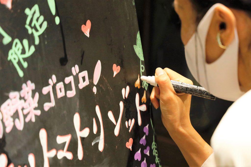 黒い看板にロービジョンのスタッフがカラフルなペンで文字を書いている画像