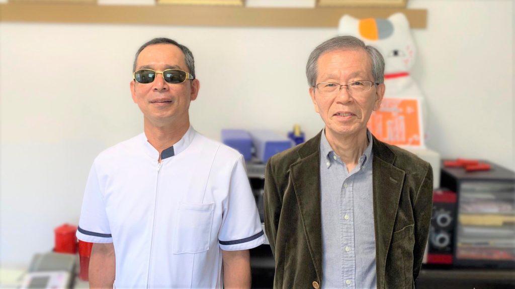 治療院の中で清水さんと牟田口先生が立って並んでいる画像。