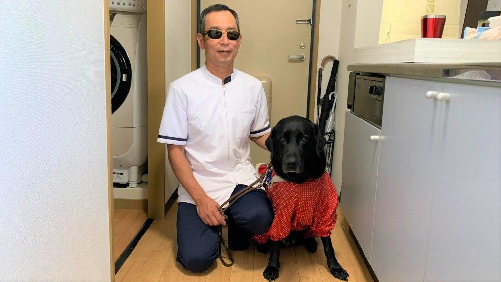 治療院の廊下で清水さんと盲導犬を一緒に撮影した画像
