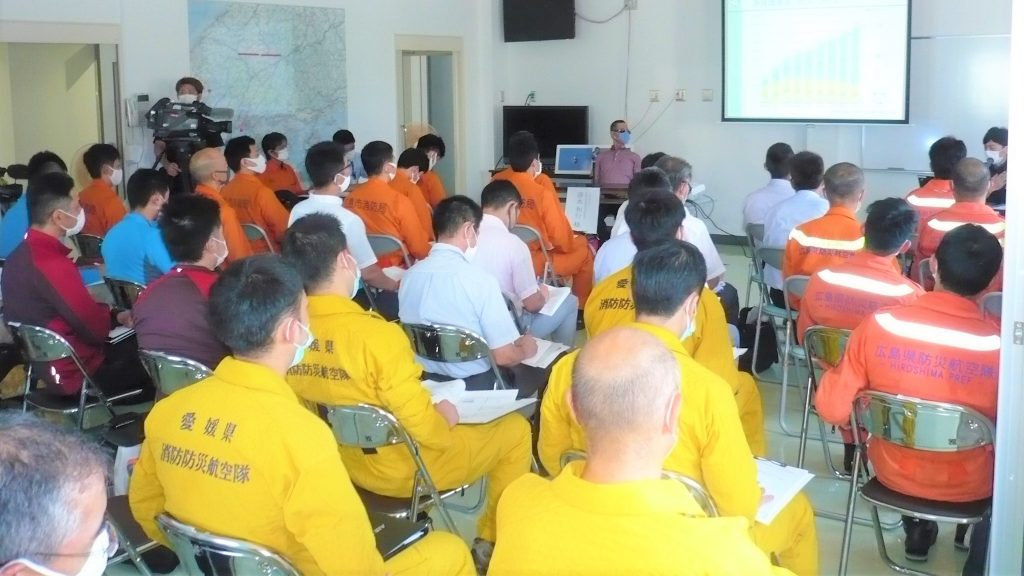会議室で消防隊に研修を行っている清水さんの画像。