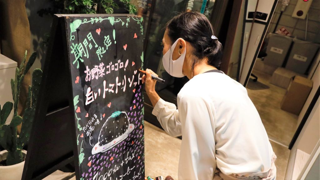 ロービジョンのスタッフが黒い黒板にカラフルなペンで文字を書いている画像。