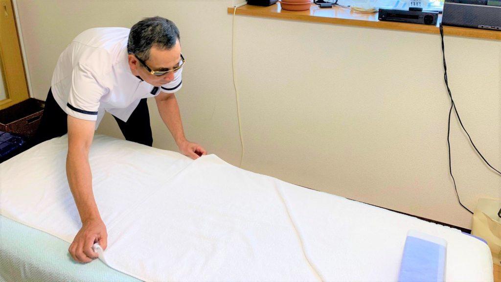 治療院のベットのシーツを整える清水さんの画像