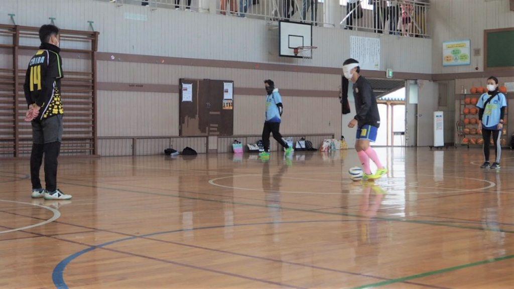 選手のヤスさんがアイマスクをしてブラインドサッカーのドリブルを披露している様子。