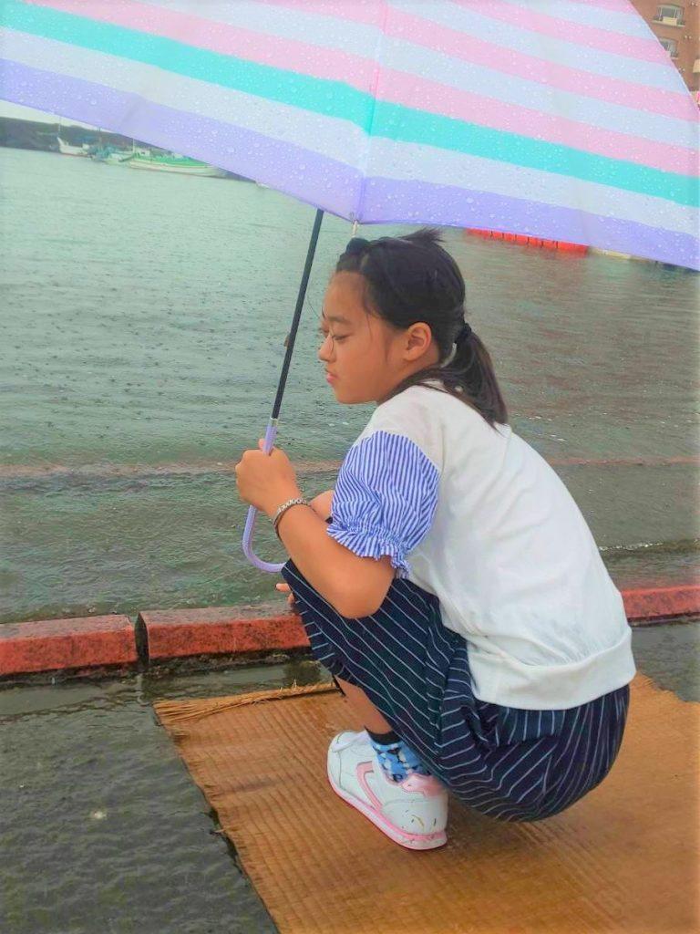 傘をさして水の上に浮かぶ板に座っている女の子の画像。