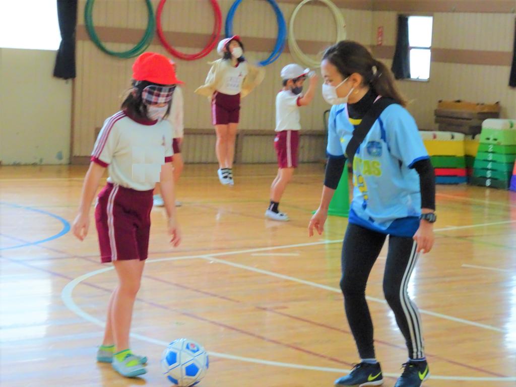 アイマスクをしてブラインドサッカーのボールをける子どもと横で見守るチームスタッフの画像。
