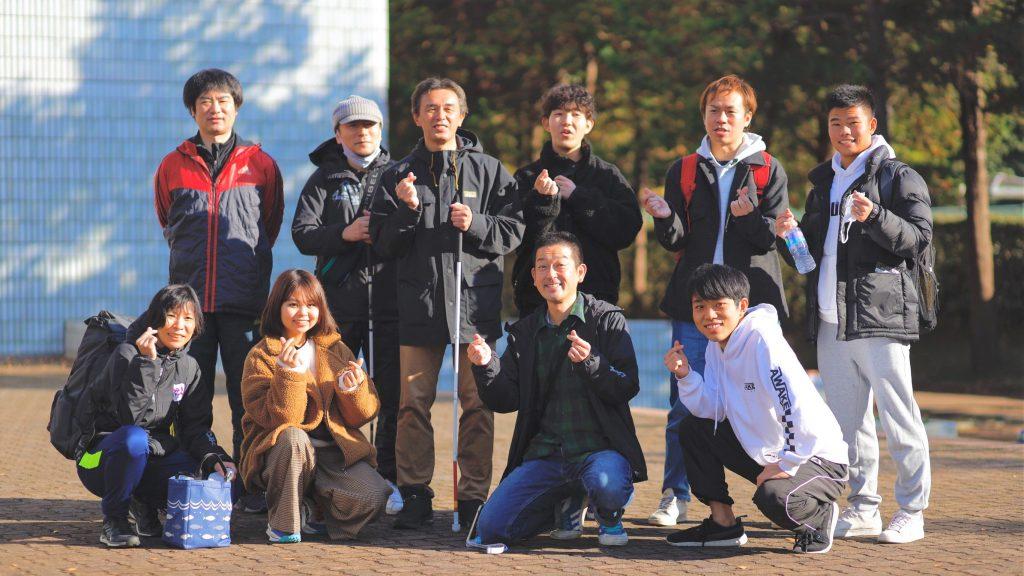 葭原さんがブラインドサッカーチーム乃木坂ナイツのメンバーと一緒に笑顔で記念撮影している画像。