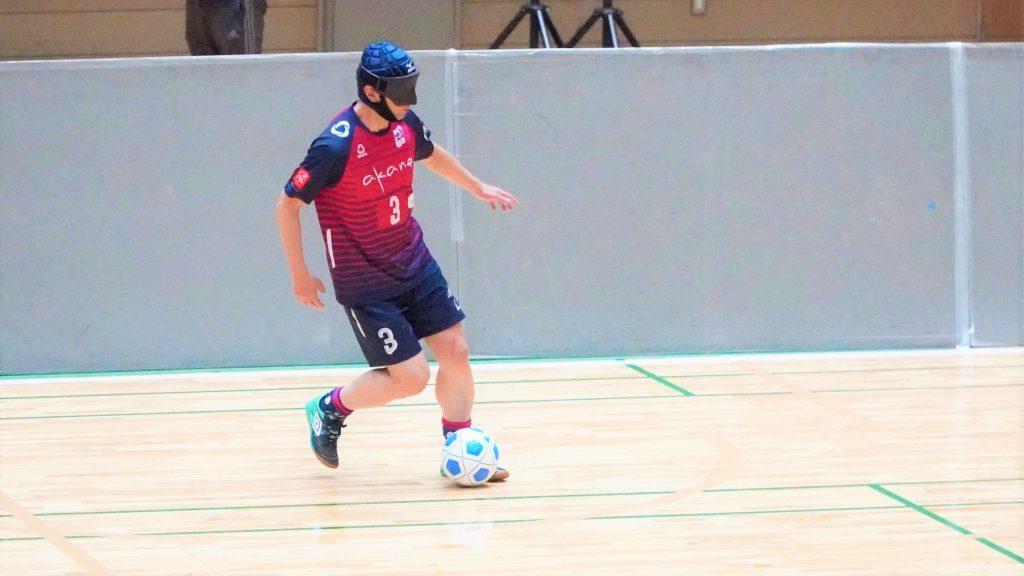 ブラインドサッカーの試合でドリブルをする葭原さんの画像。