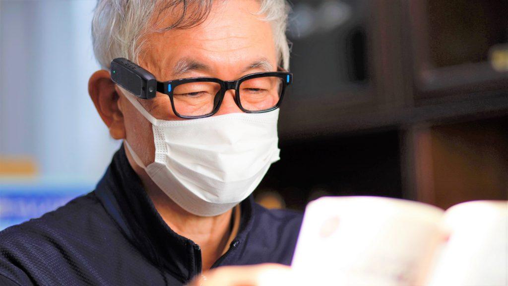 小菅さんがエンジェルアイスマートリーダーをつけて本を読んでいる画像。