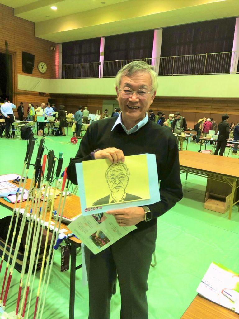小菅さんが立体コピーの似顔絵を持って笑顔で立っている画像
