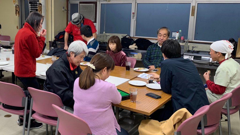 調理室で参加者がパンを食べながら談笑している画像。