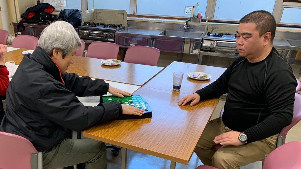 視覚障害者と晴眼者が、触って分かるオセロをしている画像。