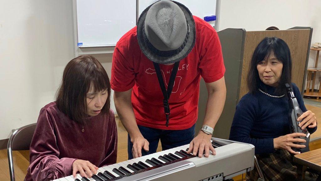 佐野さんが視覚障害者にエレクトーンの弾き方を教えている画像。