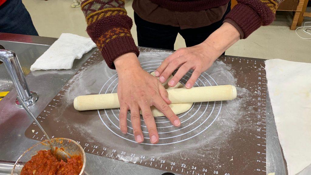 麺棒を使ってピザの生地を伸ばしている画像。