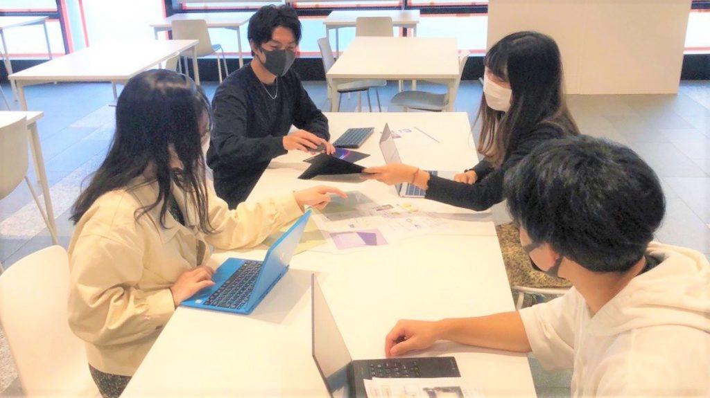 メンバー4名がテーブルを囲んで議論している画像