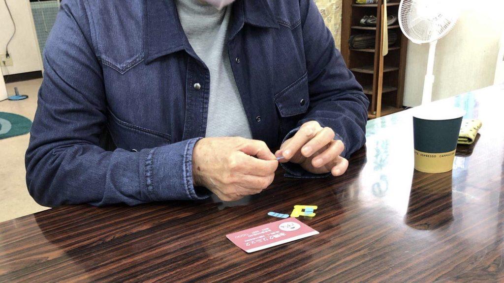 デコペタシールを触る視覚障害者の手元を撮影した画像。