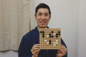 囲碁盤を笑顔で掲げる柿島さん