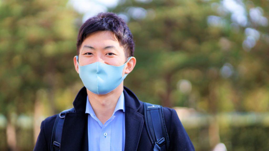 公園で高橋さんが笑顔で立っている画像。