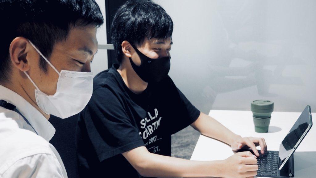 三輪くんと高橋さんが横並びに座り笑顔で作業している画像