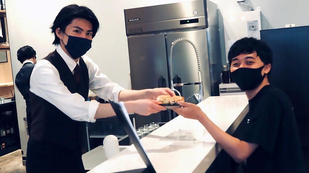 シェアオフィスに併設するカフェで店員さんからスコーンを受け取る三輪くんの画像